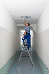 Full length side view of electrician on stepladder installs lighting to the ceiling in office